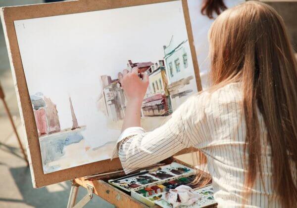 Du siehst das Bild eines Mädchens mit rotem langem Haar, das an einer Staffelei sitzt. Es malt eine Häuserfront in Aquarell.Malen stärkt die Seele