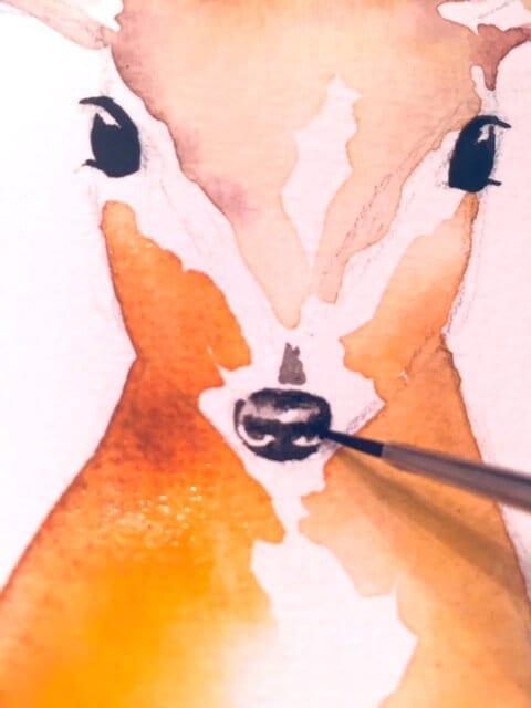 Die Illustration des Reh entwickelt sich weiter. Du siehst wie Dodo die Schnauze des Rehs in der Aquarellfarbe Elfenbeinschwarz malt