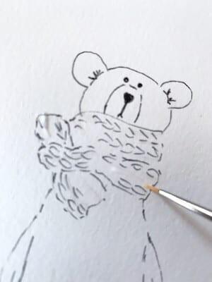 Man sieht einen Bären, gemalt von Dodo Kresse, hier das Auftragen des Rubbelkrepp