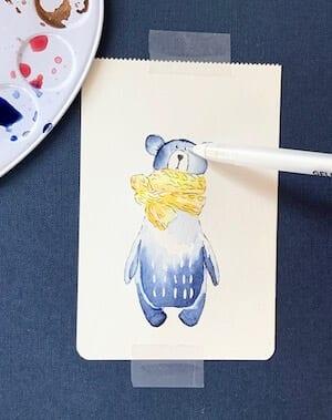 Man sieht das Bemalen der Augen des Bären mit weißem Gelstift