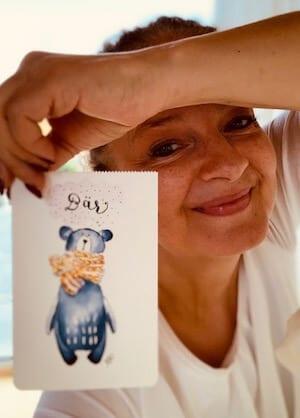 """Man sieht die lachende Künstlerin Dodo Kresse mit der Grußkarte """"Bär"""" für Creative Clb"""
