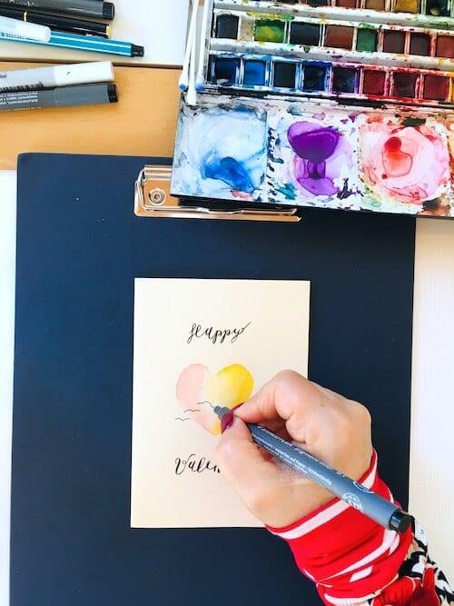 Valentinstag ist der Tag für Grußkarten an liebe Menschen. Dodo Kresse kreiiert hier eine Klappkarte mit Aquarellfarben i Rosa und Gelb. Verziert wird die Karte mit drei schwarzen Schwalben.