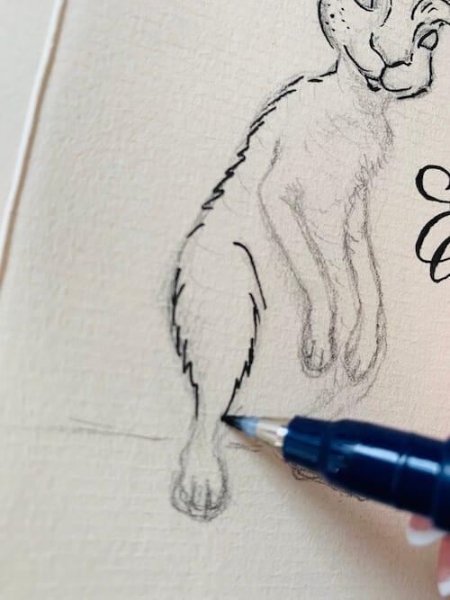 Hier siehst du, wie die Künstlerin Dodo Kresse den Hasenfuss mit Fineliner nachzieht