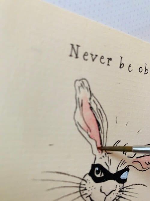Hier siehst du, wie Dodo Kresse das Hasenohr mit Krapplack Rosa ausmalt