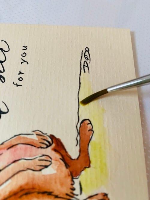 Du siehst, wie Dodo mit einem Aquarellpinsel Nr. 2 die grüne Wiese malt