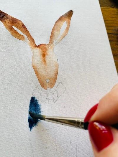 Man sieht wie Dodo Kresse Indigo in das Sakko des Hasen auf der Osterkarte fließen lässt.