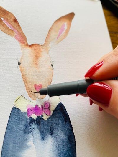 Man sieht wie Dodo die Schnurrbarthaare der Osterkarte zeichnet