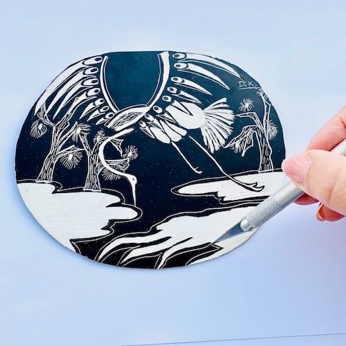 Man sieht, wie die Künstlerin Dodo Kresse mit einem Kratzmesser weiße Flächen aus einem Schabekarton ritzt.