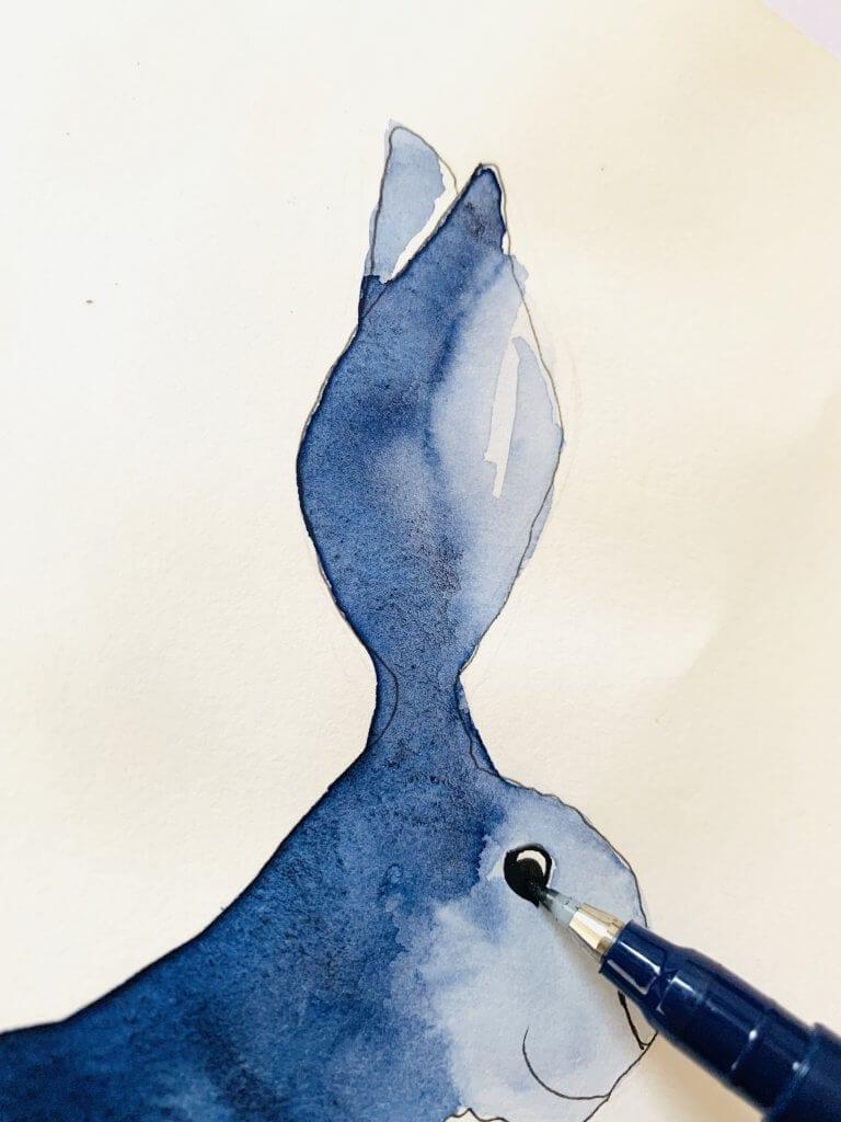 Man sieht auf diesem Bild, wie Dodo die Augen des Osterhasen mit schwarzem Fineliner zeichnet