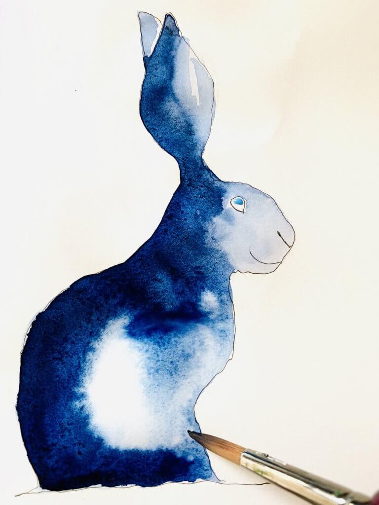 Man sieht das Aquarell des Osterhasen, wobei die Farbe Indigo-Blau nun aufgetragen wurde.
