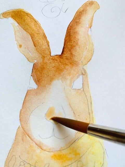 Das Bild zeigt, wie Dodo die Hasenschnauze mit Ocker ausmalt.