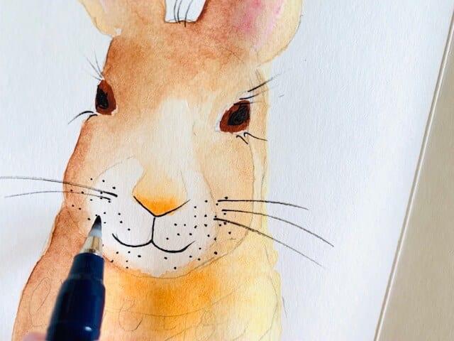 Man sieht, wie Dodo die Schnurrbarthaare des Hasen malt. Sie verwendet einen Calligraphy-Stift von Tombow, mit dem sie auch die Schrift lettert.