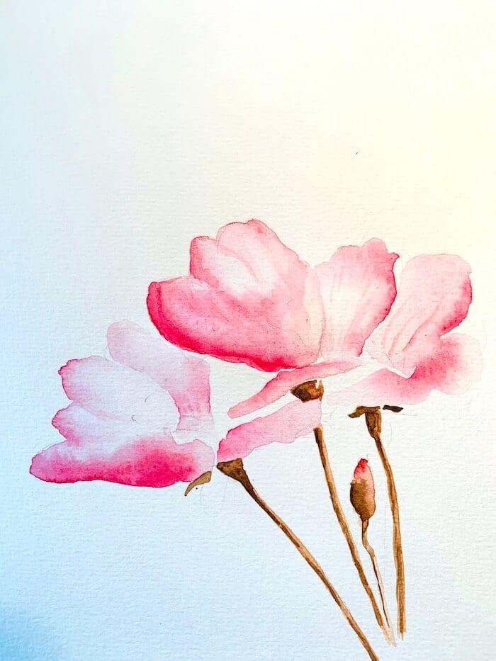 Hier siehst du schon die Zweige der Kirschblüte in Aquarellfarbe in verschiedenen Braun-Tönen gemalt.