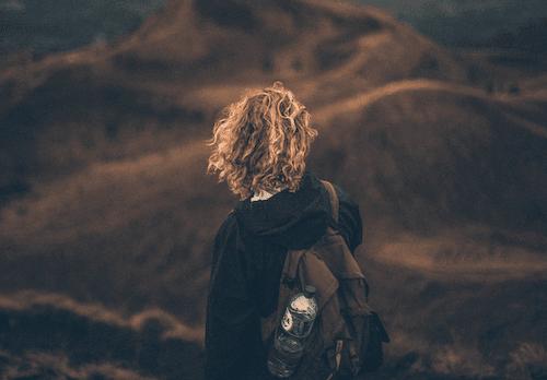 Du siehst ein Foto einer Frau, die auf einem Berggipfel steht. Lebendig sein, kreartiv sein, das sind Themen, die uns dazu einfallen