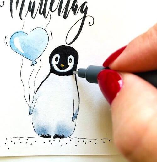 Du siehst hier, wie Dodo den Pinguin auf der Muttertagskarte mit einem Fineliner korrigiert. Aquarell kann man mit Fineliner sehr gut im Nachhinein ausbessern.