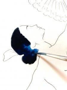 Du sieht, wie Dodo den Haarknoten der Tango-Tänzerin mit Indigo-Blau in Aquarell malt.