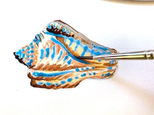 Um die Muschel  mit Aquarell malen zu können, wird mit Lasuren gearbeitet. Du siehst wie dodo die Aquarellfarbe Umbra gebrannt auf die trockene Lasue des Chinacridon golden aufträgt