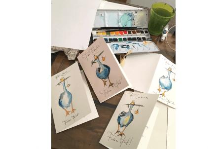 Du siehst vier Weihnachtskarten mit Gundel Gans, die mit Aquarellfarben koloriert wurden und einen Aquarellkasten auf einem Schreibtisch