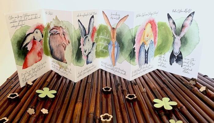 Du siehst den Osterkarte Leporello aufgefaltet auf einer Holzmatte mit Osterdeko. Du kannst diese Osterkarte online bestellen!