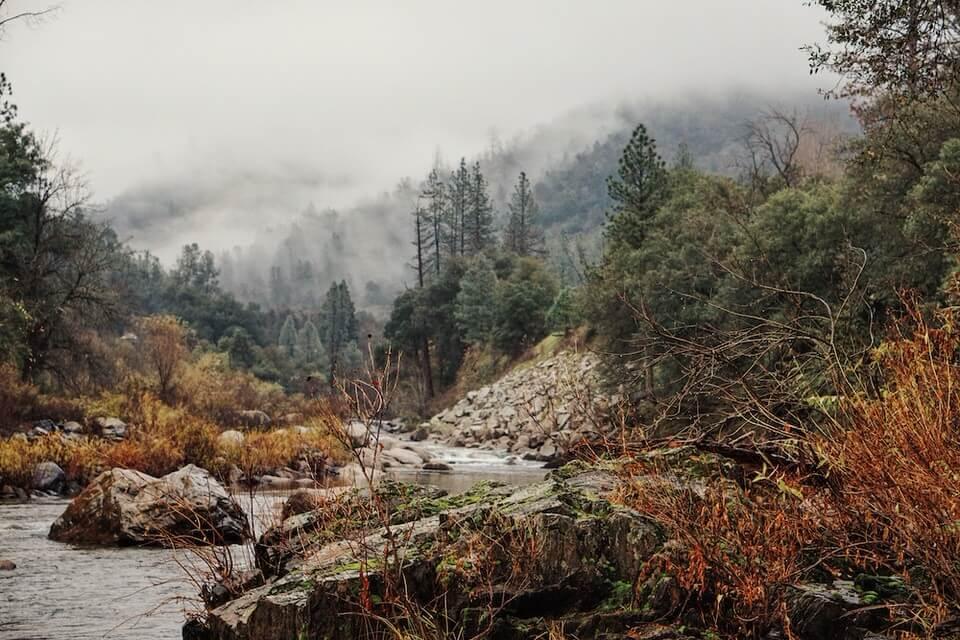 Du siehst ein Foto einer Flusslandschaft mit viel Geröll und Tannenbäumen, das zu meinem Gedicht vom April sehr gut passt.