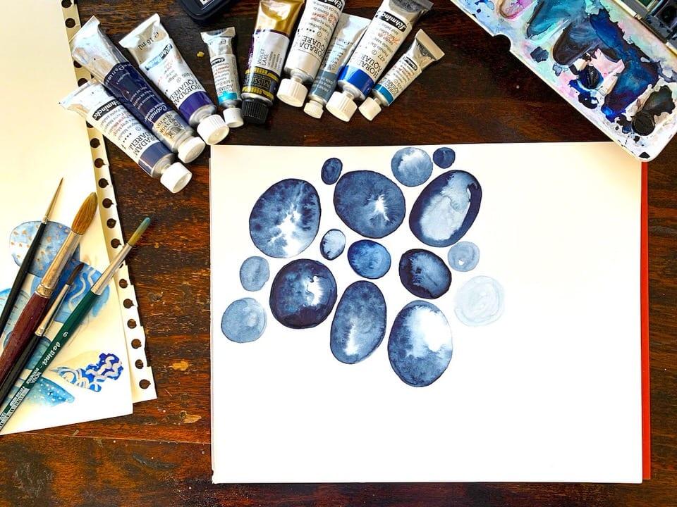 Du siehst das Coverbild des Blogartikels über das Doodling mit Indigo, Farbtuben, Pinsel, das angefangene Aquarell und einen Aquarellfarbkasten