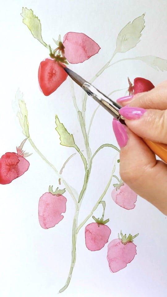 Die ersten Erdbeeren werden mit roter Aquarellfarbe gemalt