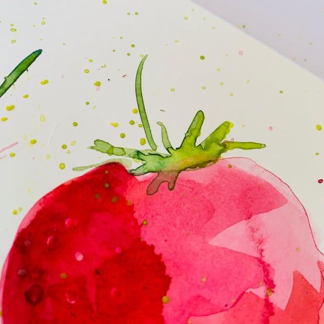 du siehst die hellgrünen Aquarellfarbe-kleckse rund um den Stiel der Erdbeeren