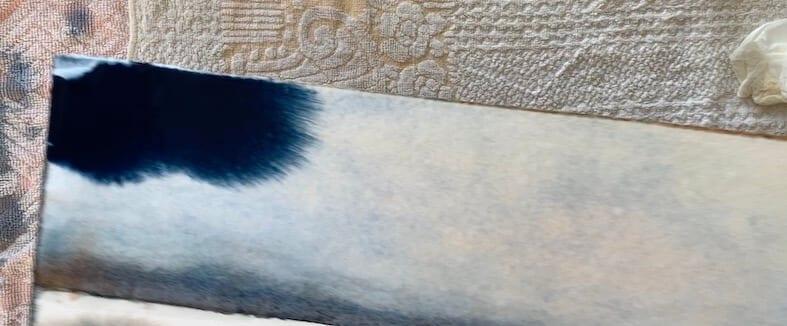 dunkelblaue Aquarellfarbe wird im Wasser aufgetragen